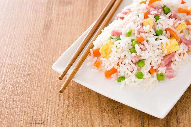 Chinesischer gebratener reis mit gemüse und omelett auf holztisch