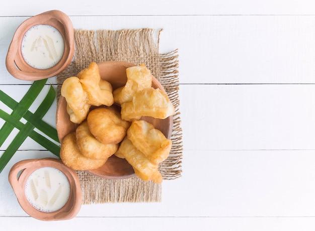 Chinesischer gebratener teig oder youtiao und sojamilch mit hölzernem hintergrund für thailändisches frühstück. thailändisches lebensmittelkonzept.