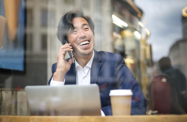 Chinesischer geschäftsmann, der mit dem laptop von einer kaffeestube arbeitet