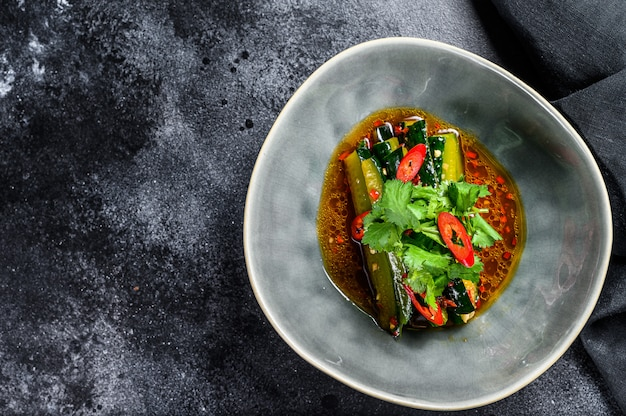 Chinesischer gurkensalat mit chili, knoblauch, sojasauce und sesamöl. draufsicht. speicherplatz kopieren