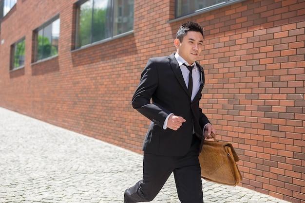Chinesischer junger geschäftsmann, der in eine stadtstraße läuft