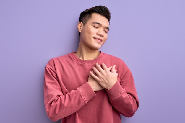 Chinesischer junger mann, der dankbarkeit ausdrückt und hände auf brust hält