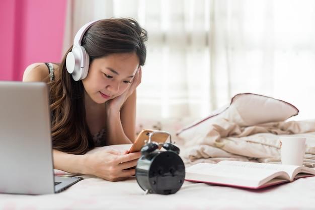 Chinesischer mädchenspiel smartphone auf bett