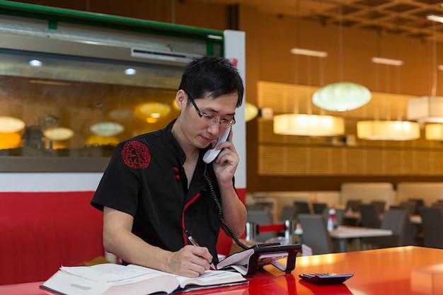 Chinesischer mann, der am telefon spricht.