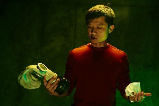 Chinesischer mann, der atemschutzmaske hält. luftverschmutzung-konzept