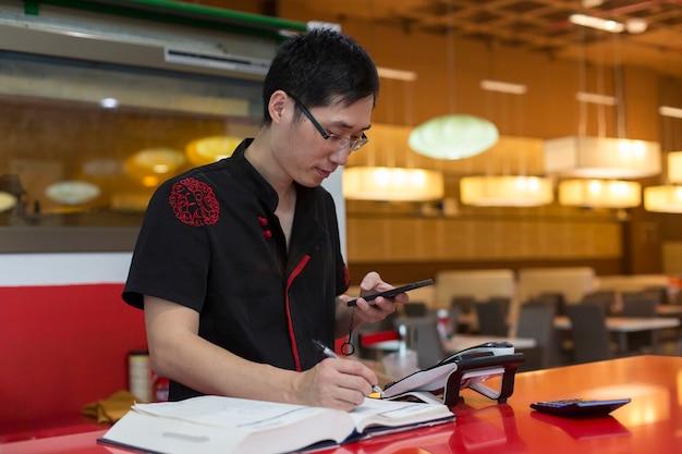 Chinesischer mann, der das handy am schalter am eingang eines chinesischen restaurants überprüft.