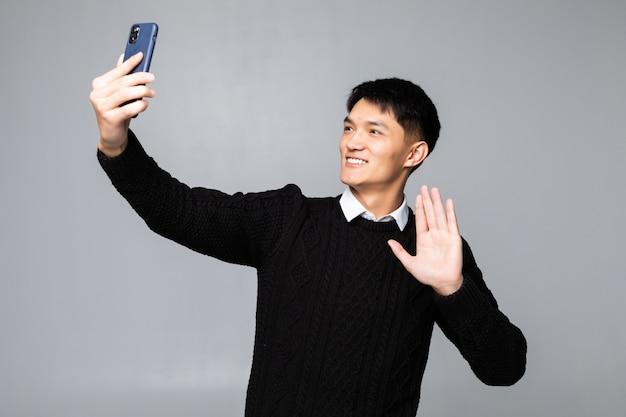Chinesischer mann, der ein selfie auf isolierter weißer wand macht