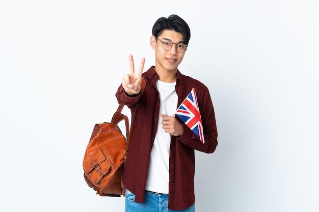 Chinesischer mann, der eine britische flagge lokalisiert auf der lila wand hält, die lächelt und siegeszeichen zeigt