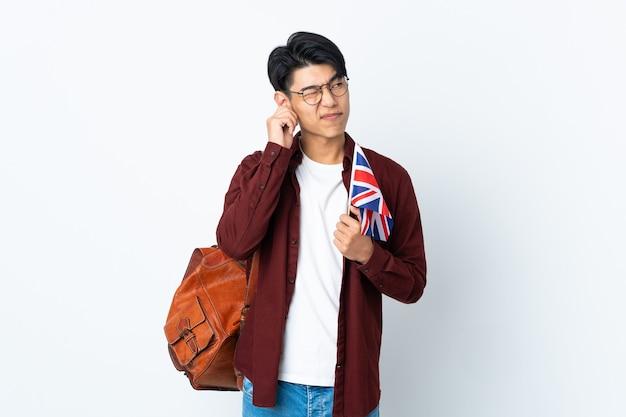 Chinesischer mann, der eine britische flagge lokalisiert auf lila wand frustriert hält und ohren bedeckt