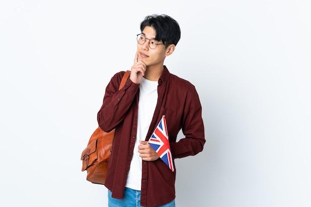 Chinesischer mann, der eine britische flagge lokalisiert auf lila wand hält, die eine idee beim nachschlagen denkt