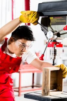 Chinesischer mann, der mit bohren herein fabrik arbeitet