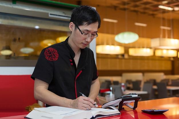 Chinesischer mann, der notizen macht