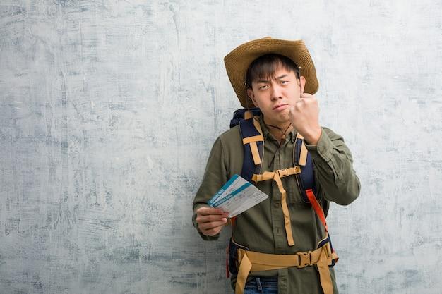 Chinesischer mann des jungen forschers, halten flugtickets, die der front faust, verärgerten ausdruck zeigen