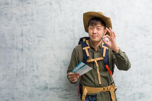 Chinesischer mann des jungen forschers, halten flugtickets nett und überzeugt, okaygeste tuend