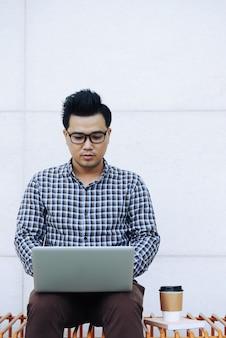Chinesischer mann in den gläsern, die draußen auf bank sitzen und laptop verwenden