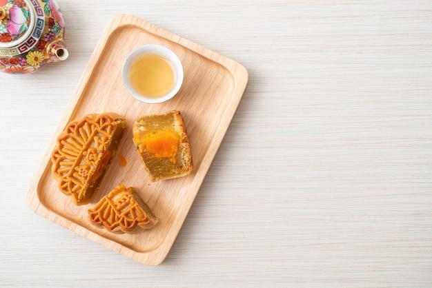Chinesischer mondkuchen durian und eigelb-geschmack mit tee auf holzplatte