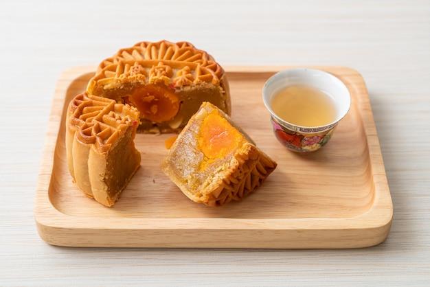 Chinesischer mondkuchen durian und eigelbgeschmack mit tee auf holzteller