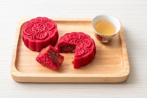 Chinesischer mondkuchen erdbeer-rot-bohnen-geschmack auf holzplatte