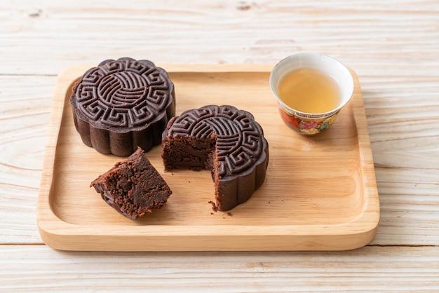 Chinesischer mondkuchen mit dunklem schokoladengeschmack auf holzplatte