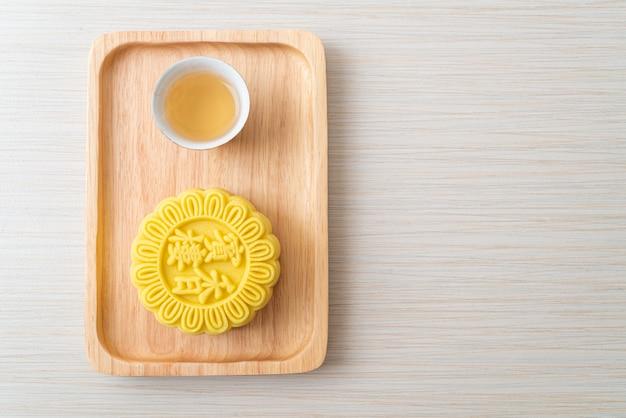 Chinesischer mondkuchen-pudding-geschmack mit tee auf holzplatte