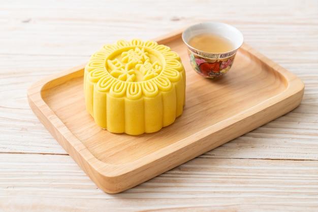 Chinesischer mondkuchenpuddinggeschmack mit tee auf holzteller