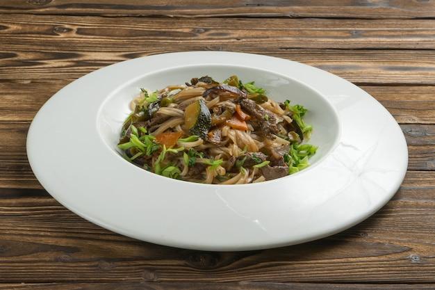 Chinesischer reisnudel-wok mit rindfleisch, gemüse und frühlingszwiebeln.