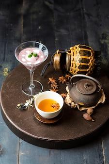 Chinesischer tee, garniert mit sternanis, serviert mit brombeerpudding