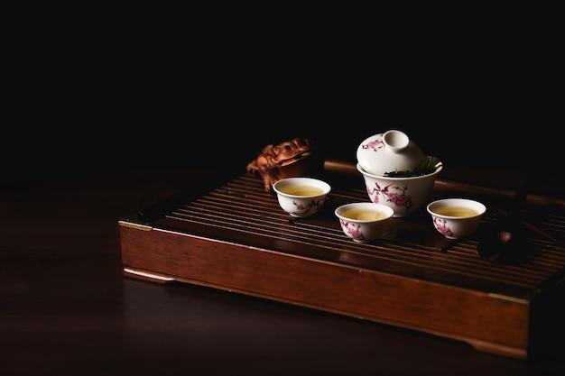Chinesischer tee stellte auf teeschreibtisch chaban auf schwarzem hintergrund ein. chinesische teezeremonie.