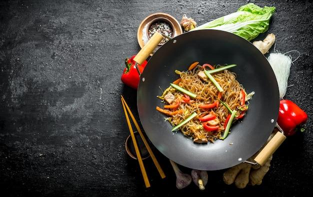 Chinesischer wok. bereiten sie funchoza nudeln mit gemüse und zutaten für die zubereitung vor. auf schwarzer rustikaler oberfläche