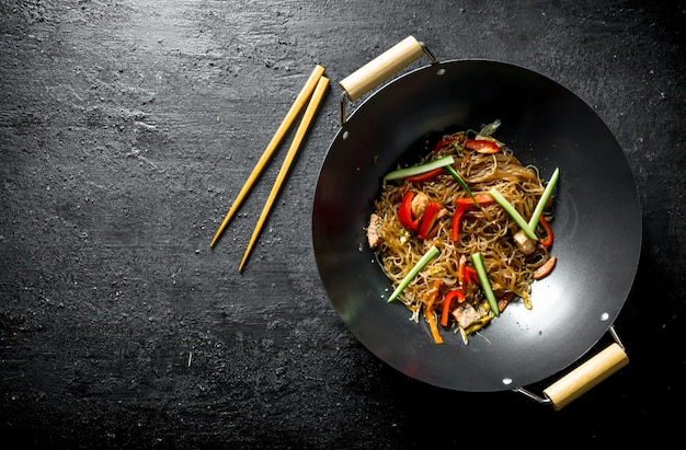 Chinesischer wok. heiße asiatische cellophan-nudeln in einer pfanne wok. auf dunklem rustikalem tisch