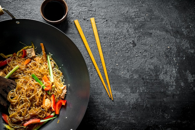 Chinesischer wok. leckere cellophan-nudeln mit lachs in austernsauce. auf schwarz rustikal
