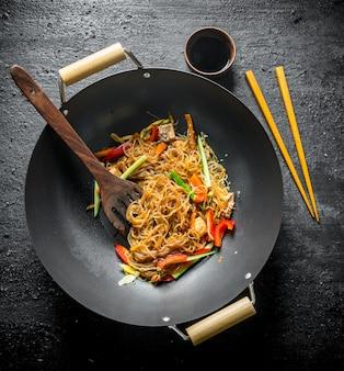 Chinesischer wok. leckere cellophan-nudeln mit lachs in austernsauce. auf schwarzem rustikalem tisch