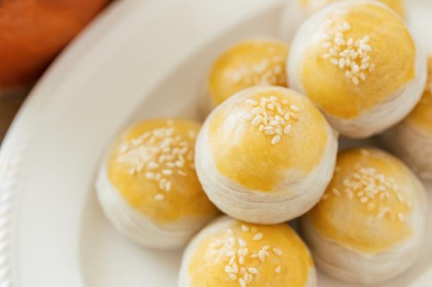 Chinesisches blätterteig oder mooncake füllten süße mungobohnenpaste und gesalzenes eigelb auf weißer platte