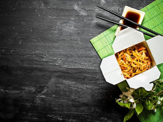 Chinesisches essen . nudeln mit garnelen, gemüse und sesam mit sojasauce.