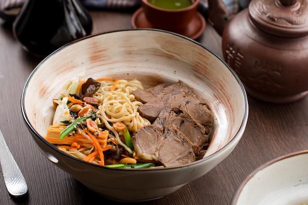 Chinesisches essen: rindfleisch mit nudeln und erdnüssen