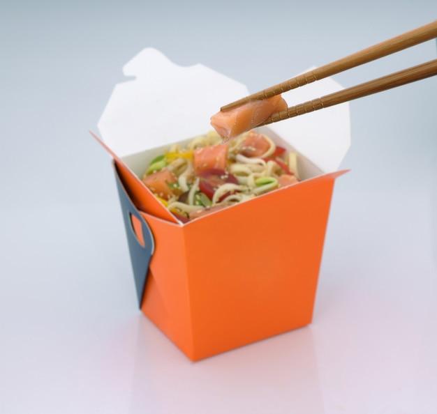Chinesisches essen zum mitnehmen nudeln mit fleisch und gemüse in einem karton auf hellem hintergrund