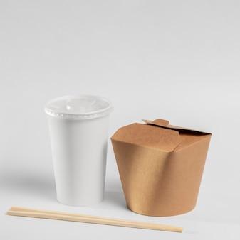 Chinesisches fast-food-paket mit stäbchen und tasse