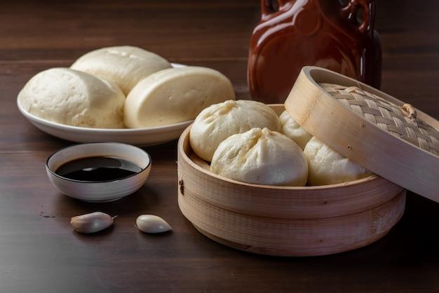 Chinesisches frühstück. gedämpfte brötchen und brei liegen auf dem tisch