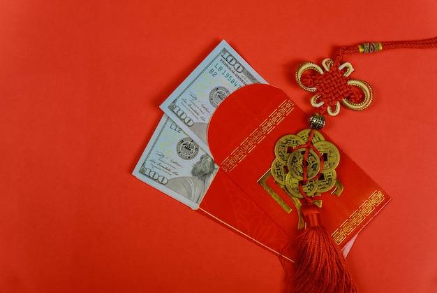 Chinesisches grußgeschenk des neuen jahres, oben geschlossen von den us-dollar banknoten in den roten traditionellen umschlägen