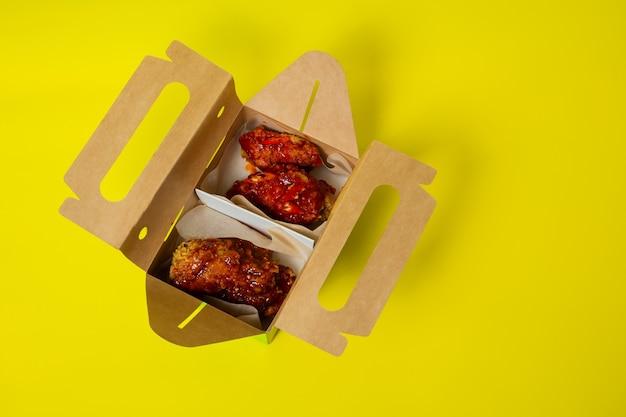Chinesisches huhn zum mitnehmen mit tomaten in einem karton fotografiert auf gelbem grund