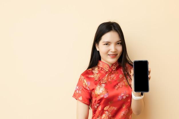 Chinesisches jugendlich mädchen, das smartphone zeigt, das traditionelles qipao-tuch des leeren bildschirms anzieht.