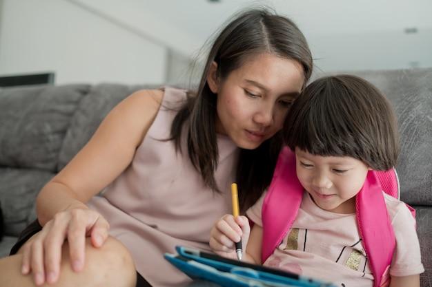 Chinesisches kind spielt smartphone mit mutter, spielt telefon, schaut cartoon, familie