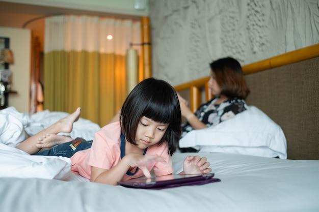 Chinesisches kind süchtig telefon, asiatisches mädchen, das smartphone spielt, kind, das karikatur beobachtet