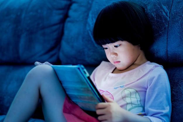 Chinesisches kind süchtig telefon, asiatisches mädchen spielt smartphone, kind telefon benutzen, cartoon beobachten