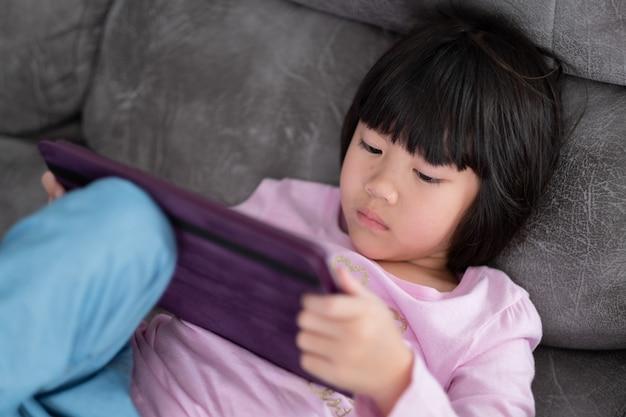 Chinesisches kindersüchtiges telefon, asiatisches mädchen, das smartphone spielt, kind, das cartoon ansieht