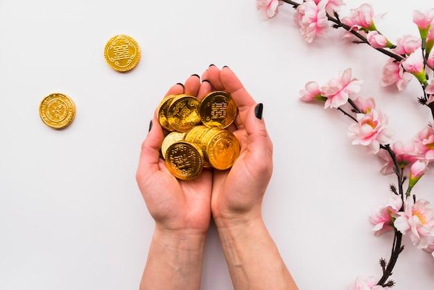 Chinesisches konzept des neuen jahres mit den händen, die münzen halten