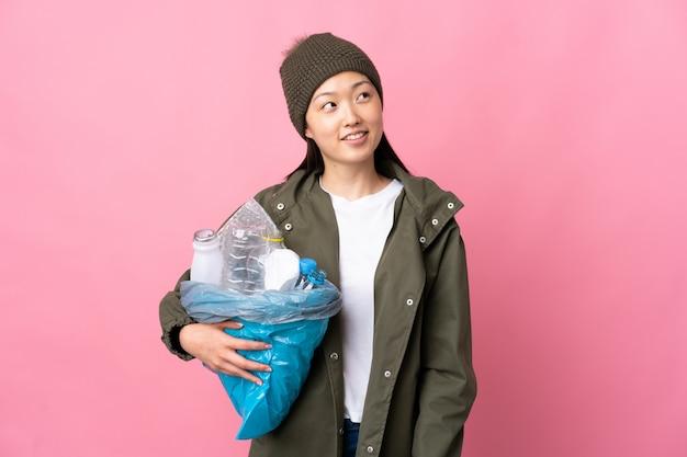 Chinesisches mädchen, das eine tasche voll von plastikflaschen hält, um auf lokalisiertem rosa nachschlagen beim lächeln zu recyceln
