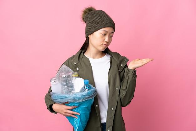 Chinesisches mädchen, das eine tasche voller plastikflaschen hält, um auf isoliertem rosa haltekopyspace mit zweifeln zu recyceln