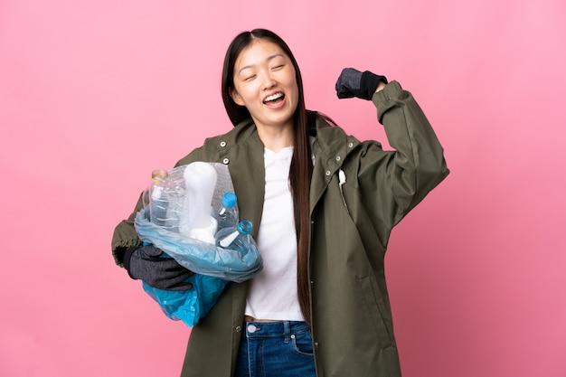 Chinesisches mädchen, das eine tasche voller plastikflaschen hält, um auf isoliertem rosa zu recyceln, das einen sieg feiert