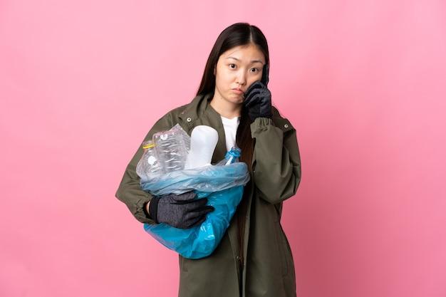 Chinesisches mädchen, das eine tasche voller plastikflaschen hält, um auf lokalisiertem rosa denken eine idee zu recyceln